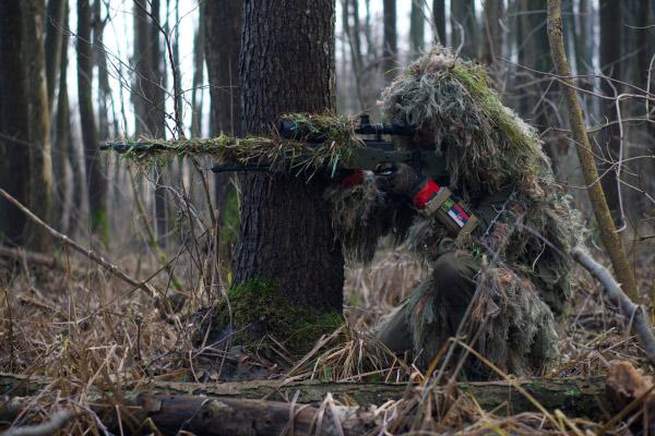 Airsoft sniper camuflado em um campo aberto